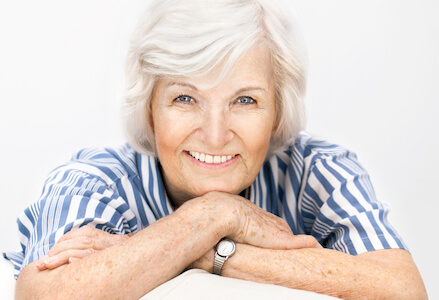 Senior woman smiles to show off how her dentures create a perfect and natural look.